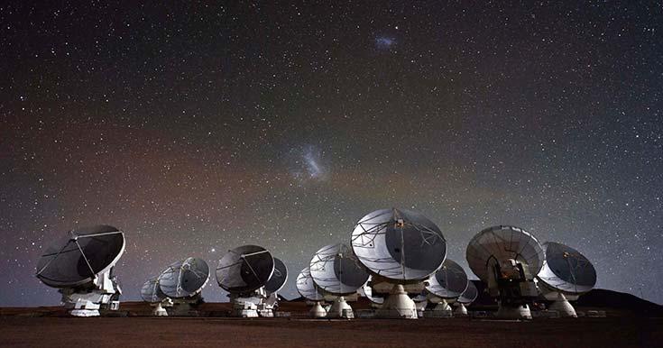 Las antenas del observatorio Atacama Large Millimeter Array (ALMA) se recortan contra las nubes de Magallanes, que se distinguen en el cielo. Las instalaciones corresponden al proyecto de radioastronomía más avanzado de este momento, cuyo telescopio está compuesto por 66 antenas como las que se ven en la foto, emplazadas a unos 5000m sobre el nivel del mar en el desierto de Atacama, en Chile. Es una colaboración internacional en la que participan instituciones de Europa, América y Japón. Foto Christoph Malin, European Southern Observatory, http://www.almaobservatory.org/en/visuals/ images?g2_itemId=1480.