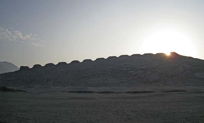 Figura 4. Salida del Sol entre las torres 12 y 13 en la mañana del 11 de enero de 2011, a las 06:51 hora local. La fotografía fue obtenida desde el punto de observación oeste, al final del corredor de la construcción excavada por los arqueólogos del proyecto (letra C en el plano). Cada seis meses el punto de salida del Sol se desplaza de una punta a la otra de la hilera de torres, pero no lo hace a velocidad constante: en los extremos, cerca de los solsticios, su movimiento es más lento que en el centro, donde está en los equinoccios. Foto AGCIENCIA