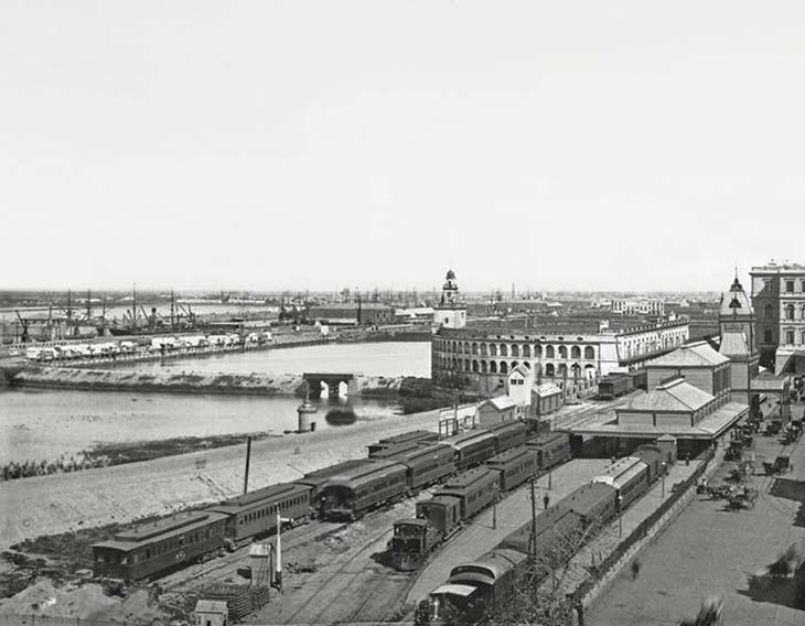 Puerto Madero y la ciudad. Foto de Arturo W Boote y Cía., ca. 1893, colección Daniel Sale. Avanzaba la construcción de Puerto Madero: los diques 1, 2 y 3 (la numeración es de sur a norte) estaban habilitados. Pronto se rellenarían los espacios inundados que muestra la foto entre el puerto y la ciudad, y desaparecerían tanto la Aduana semicircular o Aduana de Taylor (demolida en 1894) y la Estación Central de ferrocarriles (incendiada en 1897). Adviértase sobre la derecha que la ampliación de la Casa Rosada de los lados norte y este estaba concluida (cosa que sucedió en 1890).
