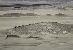 Figura 2. Tomada desde aproximadamente el mismo sitio que la foto anterior pero apuntando la cámara algo más al este, se aprecian con claridad en la foto las Trece Torres sobre una loma del desierto costero y, más allá, el valle irrigado del río Casma. El océano está a unos 15km a espaldas del fotógrafo. Foto Wikimedia Commons