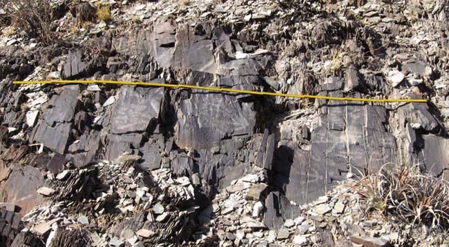 Rocas o afloramientos en que están grabados los motivos, diseminados a lo largo de unos 3km de la ladera oriental de la quebrada. Cada tramo del metro de carpintero que da la escala mide 20cm (en total 2m).