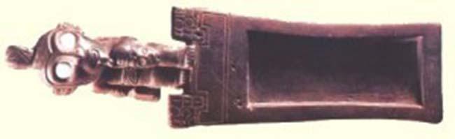 Tableta de madera con incrustaciones de turquesa en los ojos, usada para inhalar alucinógenos. Cultura Tiwanaku. Tomado de Tesoros de San Pedro de Atacama - Museo Chileno de Arte Precolombino.