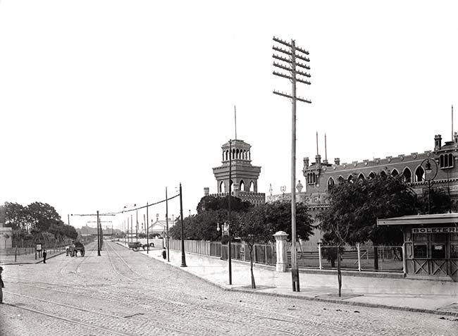 Vista de la avenida Gutenberg (hoy Luis María Campos) tomada mirando al noroeste desde su esquina con Santa Fe. Al fondo se distingue el todavía en pie puente del Ferrocarril Central Argentino (hoy Mitre). Sobre la derecha, edificios de la exposición ferroviaria.