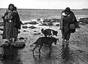 Mujeres selk'nam con perros en la costa fueguina, 1923. Foto Alberto María De Agostini, archivo Asociación de Investigaciones Antropológicas.