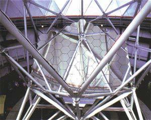 El espejo hexagonal del telescopio Hobby-Eberly de 11m colocado en el armazón del telescopio. Abajo a la izquierda, quizás, se observen dos personas junto a la base del telescopio. Foto: © Universidad de Texas en Austin.